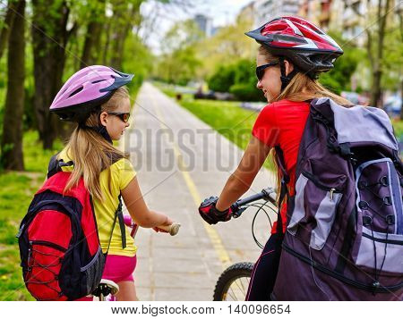 Bikes bicyclist girl. Girls wearing bicycle helmet and rucksack ciclyng bicycle. Girls children cycling on yellow bike lane. Bike share program. Back view. Bicycle girl speaking.