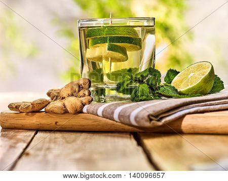Healthy detox drink with ginger . On wooden boards glass with green tea and mint. Mint ginger drink number two hundred seventy with slice lime and napkin. Country life outdoor. Light background.