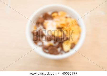 Blur of cornflakes with milk in a white bowl