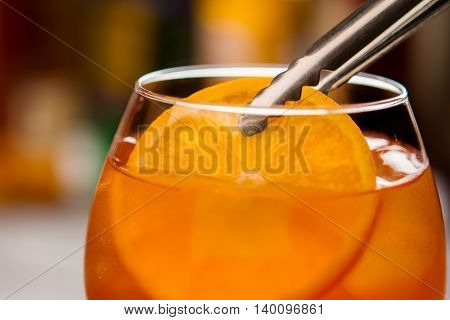 Tongs holding slice of orange. Glass filled with cocktail. Traditional recipe of aperol spritz. Sweet wine and fruit.