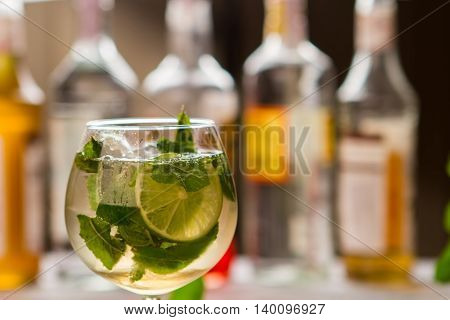 Drink with slice of lime. Mint leaves in beverage. Mineral water and citrus fruit. Special recipe of hugo cocktail.