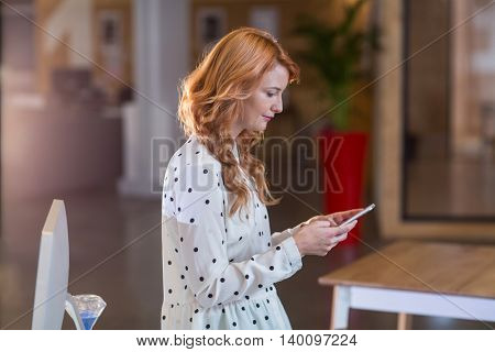 Side view of young woman using mobile phone in office