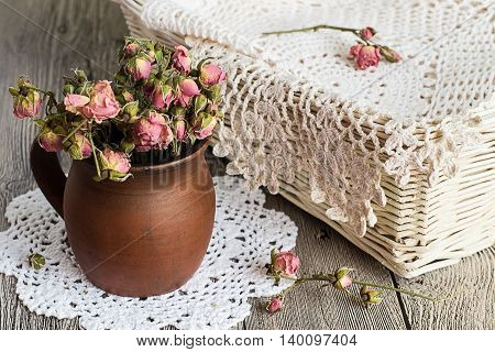 Dried flowers in an earthenware mug and crocheted napkin in a wicker basket on a gray wooden table.