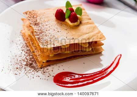 Dessert with fresh raspberries. Red sauce on white plate. Special recipe of millefeuille. Chocolate crumbs and sweet custard.