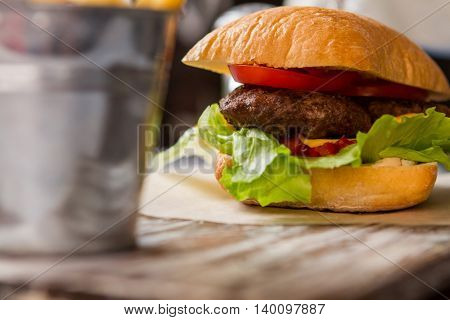 Burger with tomato slices. Buns and dark grilled meat. New dish in snack menu. Enjoy every bite.