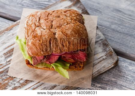 Sandwich with meat. Brown bread and lettuce. Homemade sandwich recipe. Cooked veal and fresh tomatoes.