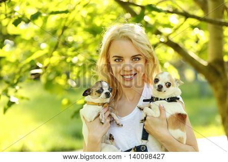 Woman holding fluffy dog in the park