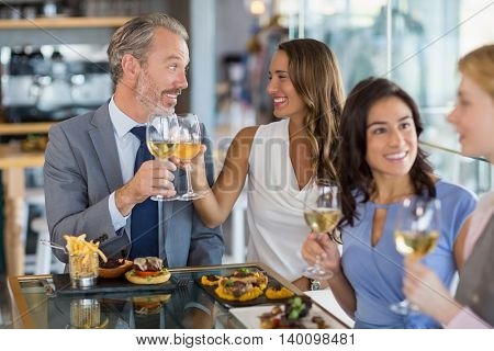 Happy business colleagues interacting and toasting beer glasses while having lunch in a restaurant