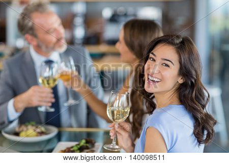 Portrait of beautiful woman holding glass of wine while toasting glasses of wine in the background