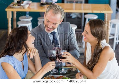 Happy business colleagues toasting wine glass in the restaurant
