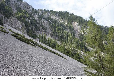 Scree is a slope of loose rock debris at the base of a steep incline or cliff, beautiful calm cloudy morning in Slovenian  Alps, Europe