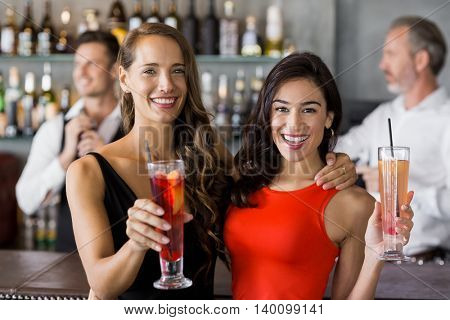 Two beautiful women holding cocktail glass in restaurant