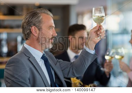 Portrait of businessman toasting his beer glass in a restaurant