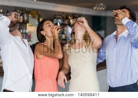 Group of friends having tequila shot in restaurant