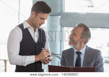 Waiter taking the order from a businessman in restaurant