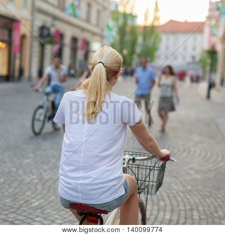 Rear view of beautiful blond caucasian woman riding cruiser bike in Ljubljana city center.
