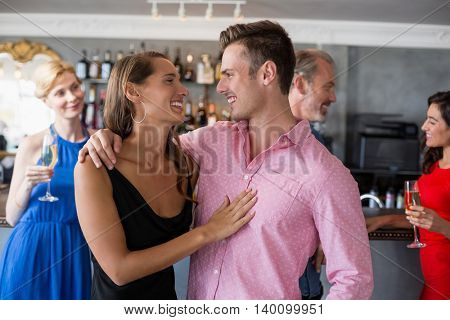Couple embracing each other in restaurant and friends standing in background