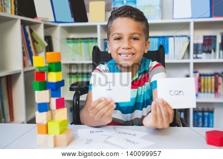 Disabled boy showing placard that reads I Can in library at school