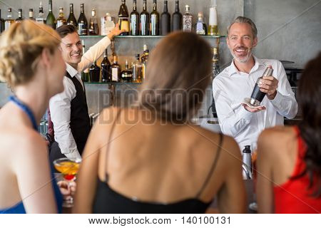 Female friends ordering drinks from barkeeper in restaurant