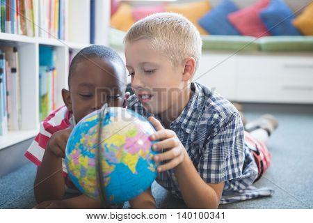 School kids lying on floor studying globe in library at school