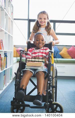 Portrait of happy schoolgirl carrying schoolboy in wheelchair in library