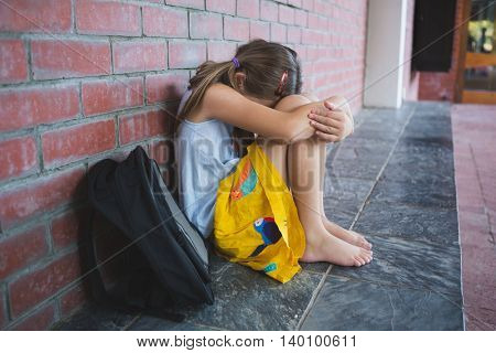 Sad schoolkid sitting alone in corridor at school