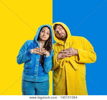 Woman in blue pijamas and man in yellow bathrobe on the blue-and-yellow background