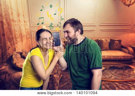 Young couple listening to music using smartphone in the room