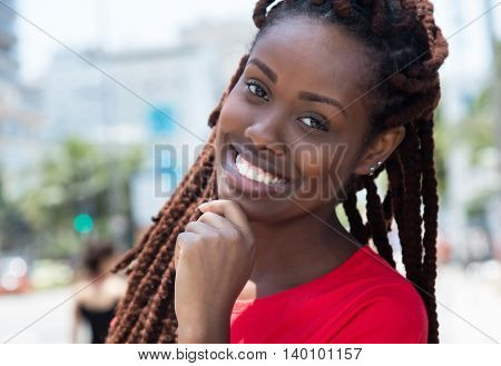 Happy african woman with dreadlocks outdoor in city in summer