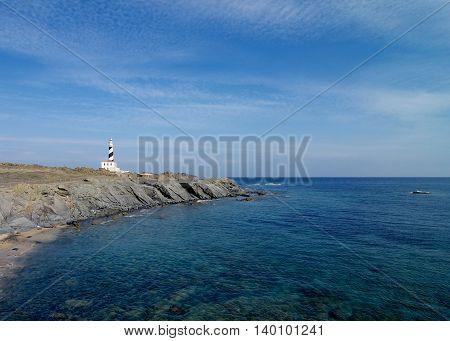 Lighthouse Cap de Favatrix with Rocky Shake Shore on Sea Waves Edge and Blue Sky background Still Life. Northern Coast of Menorca Balearic Islands
