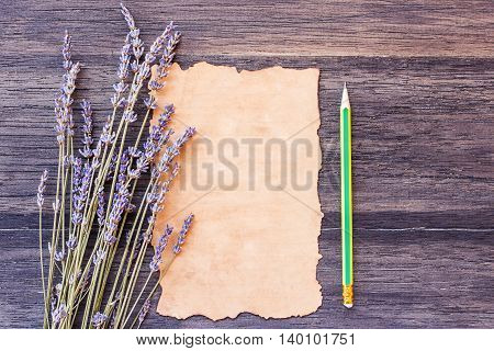 Lavender flower and old paper with pencil on the old wooden table background. top view with copy space