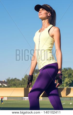 Sporty girl on the stadium. Stadium tribune. Slim sporty fitness woman. Social media and fitness concept. Toned image.
