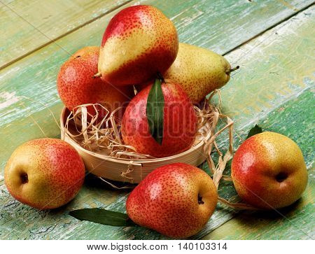 Arrangement of Ripe Yellow and Red Pears with Leafs in Wicker Bowl closeup on Cracked Wooden background