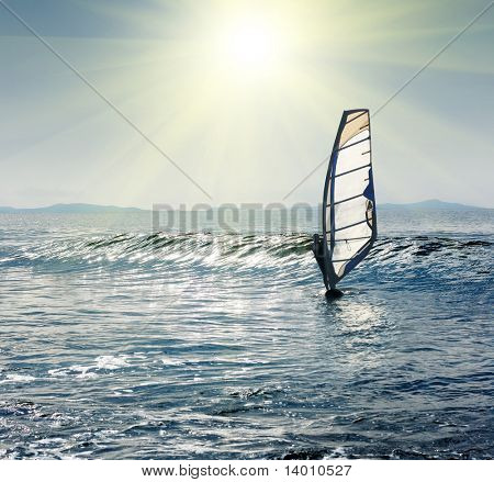 Windsurfer on sea wave under sunlight