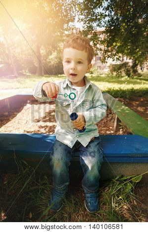 Cute little boy playing at the children playground outdoors with soap bubbles. Lens flare effect.