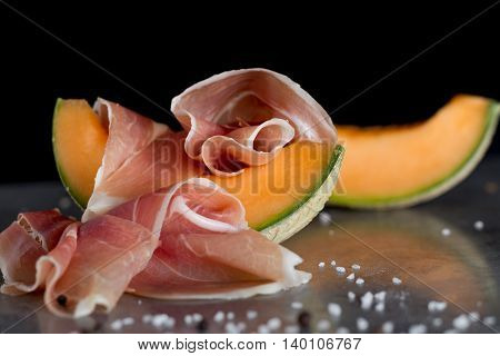 Jambon mix. Ham. Traditional Italian and Spanish salting smoking dry-cured dish - jamon Serrano and prosciutto crudo sliced with melon on grey background. Copy space. Closeup.