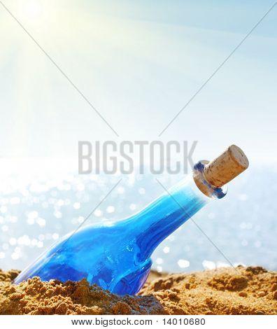 Blue bottle with cork on sea side