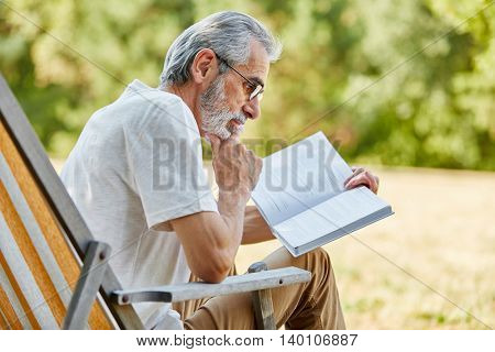 Old man reading a book on a deck chair in the park in summer