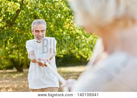 Old man playing tug of war with his wife in summer in the nature