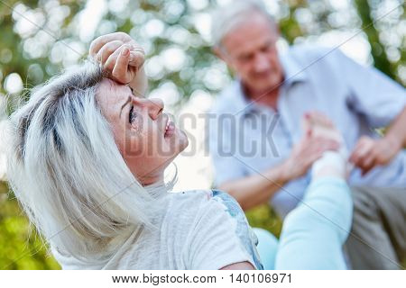 Old woman with pain on her foot while man puts a bandage on it