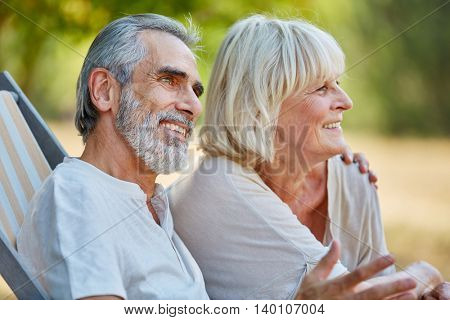 Happy senior couple in love sitting relaxed in summer in the nature