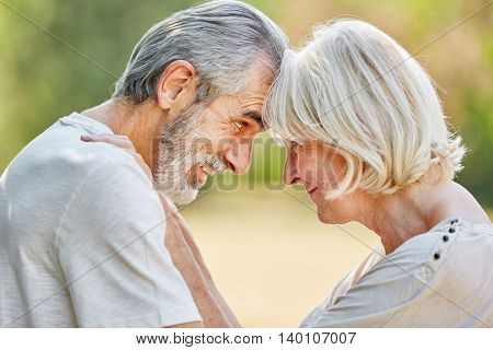 Seniors in love flirting and looking each other in the eyes in the nature