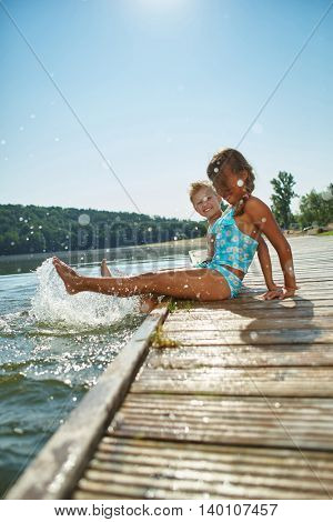 Two happy kids splashing the water in summer