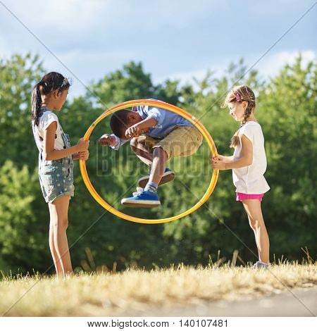 Boy jumps through hula hoop at the park while his friends hold it