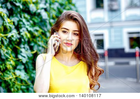 young woman talking in city sreet at summer in yellow dress at sunny day