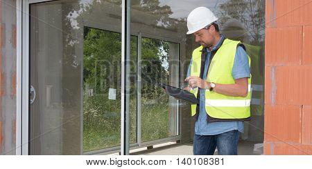 Building Entrepreneur Using Digital Tablet On Site Under Construction Outside