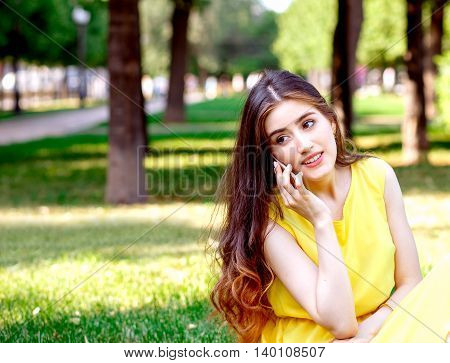 young woman talking in city park at summer in yellow dress at sunny day