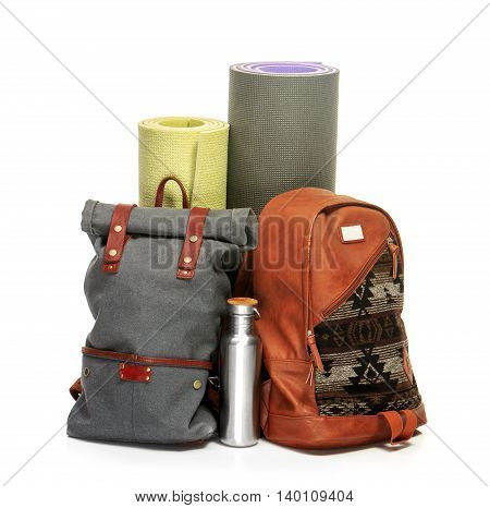 The suitcases, backpack, karrimats on white background. The travel, tourism and holidays concept