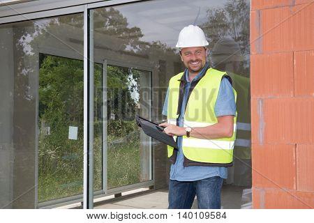 Handsome Building Entrepreneur Using Digital Tablet On Site Under Construction