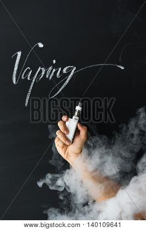Electronic cigarette in hand vaper on a dark background with smoke. New subculture vaping concept.